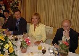 Ana Valle y su Junta Directiva junto a unas macetas con flores entregadas a las damas asistentes a la celebración